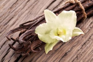 Bunch of vanilla sticks and flower on old wood.